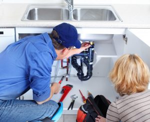 plumber-and-homeowners-inspecting-underneath-kitchen-sink